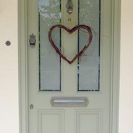 Green front door with heart shaped twig wreath