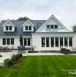 Remodelled house with white render and slate roof on a green lawn