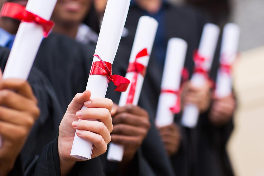 Red ribbon diplomas of graduates in line