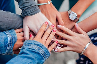 Photo of girls' hands coming together as a sign of overcoming difficulties in life.