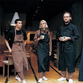 três pessoas em restaurante com uniforme profissional gastronomia avental camisa calça