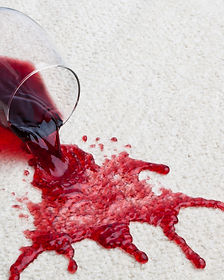 A toppled glass of red wine with a dirty
