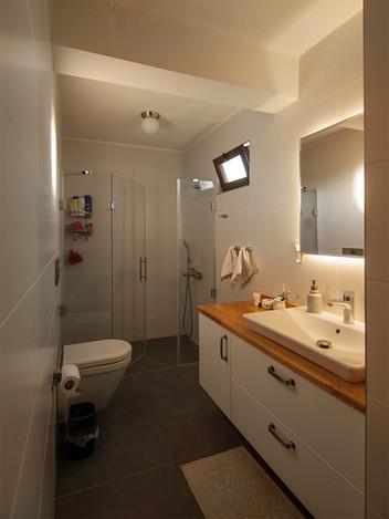 Üst kat banyo da büyütüldü ve iki bölümlü olarak tasarlandı.  Tasarlanan dolapta çanak lavabo ve masif tezgah kullanıldı. Ledli ayna tasarlanarak uygulandı. Seramikten duş yapılarak camlı duşkabinle mekanın ferahlığı sağlandı.