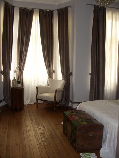 Yüksek tavanlı tarihi evde pencerelerde kadife perdeler kulanıldı. Cumba içerisine eskiciden alınmış iki koltuk renove edilerek mekana uygun renklerle döşendi.