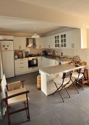 Camlı ve beyaz dolaplar, yemek bölümü ile birleştirilerek ferah bir mutfak yaratıldı.