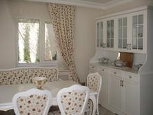 Rustik mutfağın yemek bölümünde bir vitrin dolap ve ona uygun sandalyeler tasarlandı. Perde ve koltuklarda aynı desen kumaş kullanıldı.