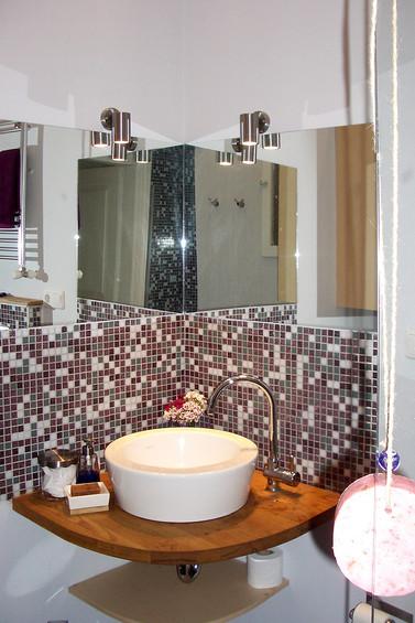 Modern bir banyo düşünülerek ahşap tezgah ve çanak lavabo yapıldı ,duvarlarında kısmi olarak mozaik ,ayna ve boya kullanıldı.