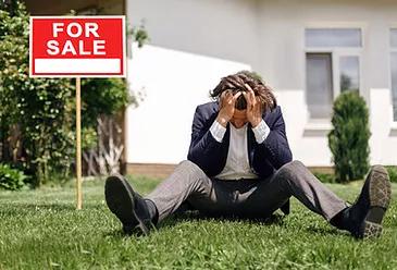 Depressed real estate agent sitting on ground.jpg