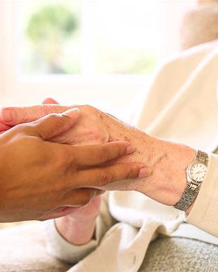 Mãos jovens, de tonalidade negra, seguram mãos envelhecidas. Demonstram acolhimento e cuidado.