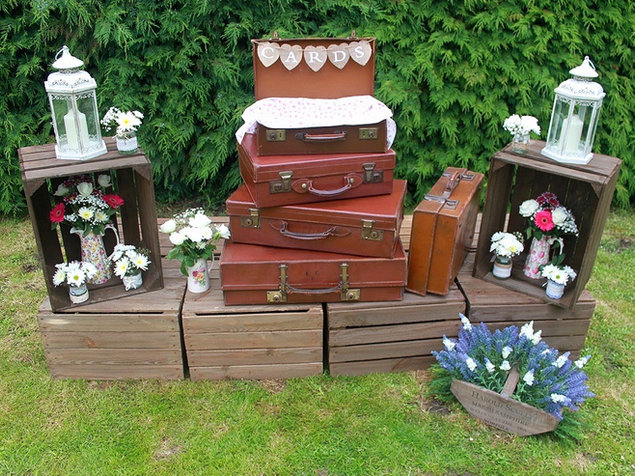 Vintage Suitcases Stacked on Rustic Crates for Wedding Venue Styling