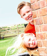 Two children looking around the corner of a wall