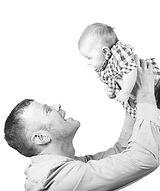 Black and White image of a father holding his baby in the air