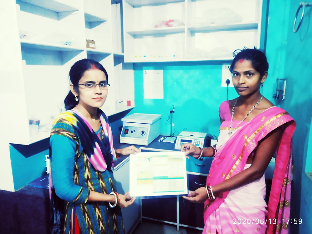 Ms Veena giving Soil Health Card to a women farmer with Harvesto Soil Testing Lab