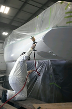 man painting fiberglass boat