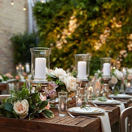 Cavalier and Company. Chicago wedding design and event party planning. Decor and rentals include rustic garden party with wooden farm house dining tables set with candles, roses, peonies, dahlias, and succulents with a living greenery wall.  Joshua Jones and Chris Junkerman.