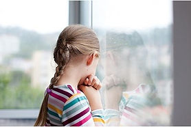 Yoiung girl staring out of a window