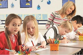 Children colouring in the classroom with teacher