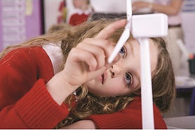 young girl lying her head on her arm playing with a small wind turbine