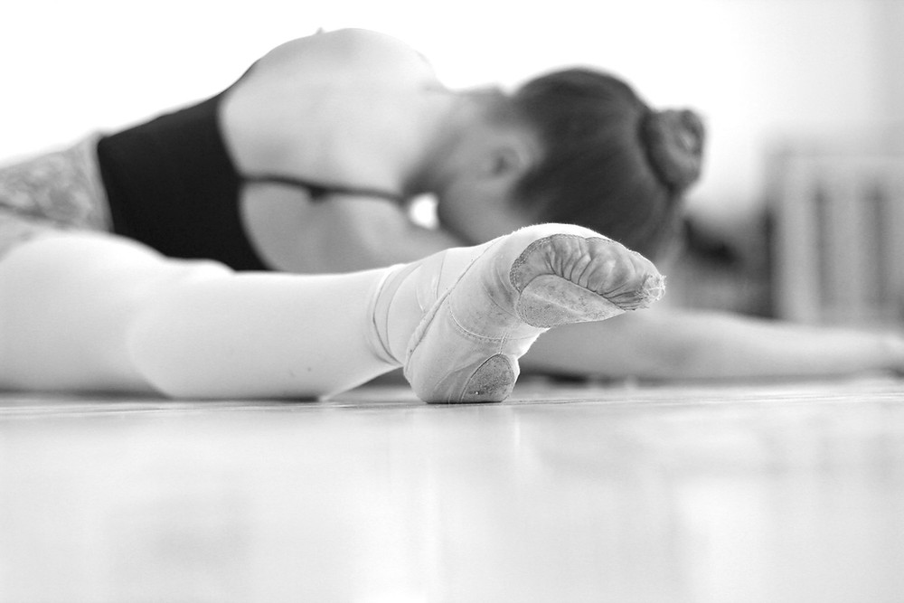 black and white image of a ballet dancer stretching