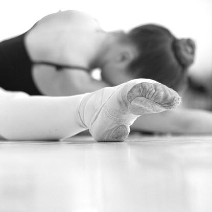 Ballerina stretching on floor