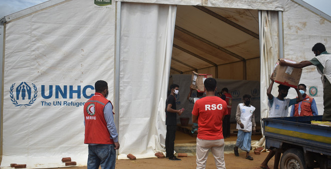 An RSG field coordinator monitors a delivery of reusable face masks to the UNHCR warehouse in Kutupalong, as a staff from distribution partner Bangladesh Red Crescent Society looks on.  © UNHCR/Md Arif Ahmed