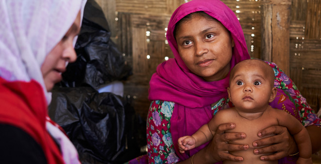 Rohingya refugee Tahara Begum, 25, right, holds her four-month-old daughter Shahana, as she speaks with a nutrition counsellor at the UNHCR counselling center in the UNHCR transit center, in Kutupalong.  Tahara, her husband and three children, including baby Shahana, endured a very difficult journey to Bangladesh after being driven from their homes by armed forces; Tahara had to give up her wedding ring in exchange for passage by boat across the Naf River.  © UNHCR/David Azia