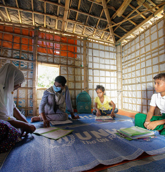 Komor Uddin, a Rohingya refugee assistant teacher at Kutupalong Learning Center, going door to door to give lessons to the Rohingya children at home due to a COVID19 lockdown. Both Bangladeshi and Rohingya volunteer teachers have played a central role in continuing to help children learn at home, engaging parents and caregivers to support learning, and providing workbooks and visual aids. © UNHCR/Hasib Zuberi