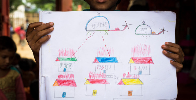 A Rohingya girl displays her finished artwork in a designated safe space for children in the Kutupalong extension site in Cox's Bazar. She and other young Rohingya refugees were asked to draw their memories of fleeing their villages, as a therapeutic exercise.  © UNHCR/Roger Arnold