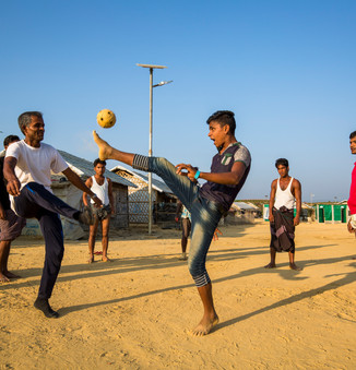 A group of young men play a game of sepak takraw, or kick volleyball, in Camp 4 Extension.  © UNHCR/Roger Arnold