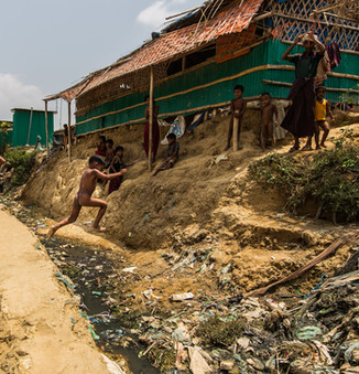 A Rohingya child jumps over a clogged open drain. Such unsanitary sights are common in the camps.  © RSG/Daniel Neo