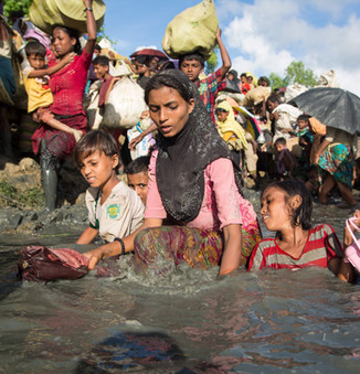 A Rohingya mother wades through water with her young children as they cross the border from Myanmar into Bangladesh, near the village of Anjuman Para in Palong Khali.  © UNHCR/Roger Arnold