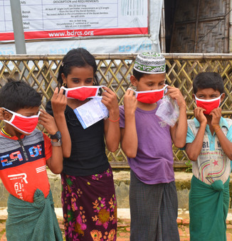 Four Rohingya children try on reusable face masks they have just received from UNHCR, that were donated by RSG and the people of Singapore.   © UNHCR/Md Arif Ahmed