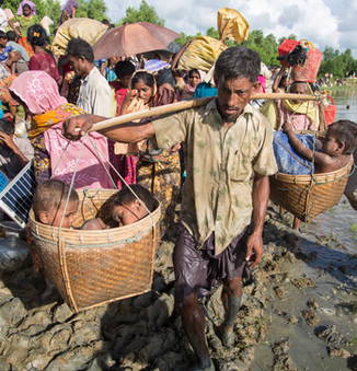 A Rohingya father carries his children in baskets as he wades through water crossing the border from Myanmar into Bangladesh, near the village of Anjuman Para in Palong Khali.  © UNHCR/Roger Arnold