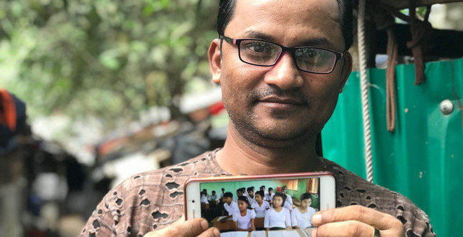 """Rohingya refugee Nur Alam shows a photo of his pupils at a school in Maungdaw, Myanmar where he was once headteacher. He said, """"I feel like crying when I see this. We didn't have freedoms in Myanmar. We do here, but I miss my students. Many who completed Grade 6 are here in the camp, working as volunteers with organisations."""" © UNHCR/Caroline Gluck"""
