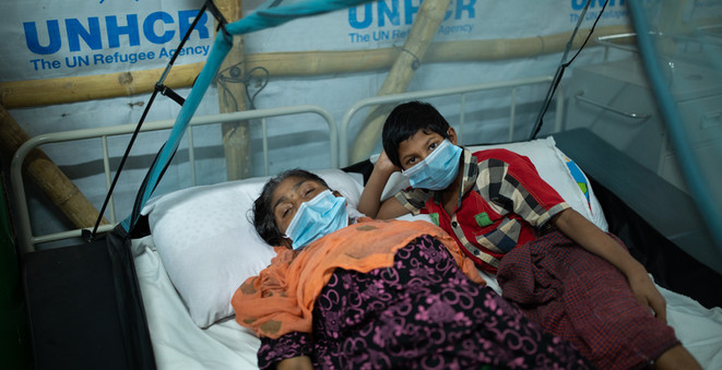 A young Rohingya keeps watch as a family member rests in a COVID-19 ward.  © UNHCR/Kamrul Hasan
