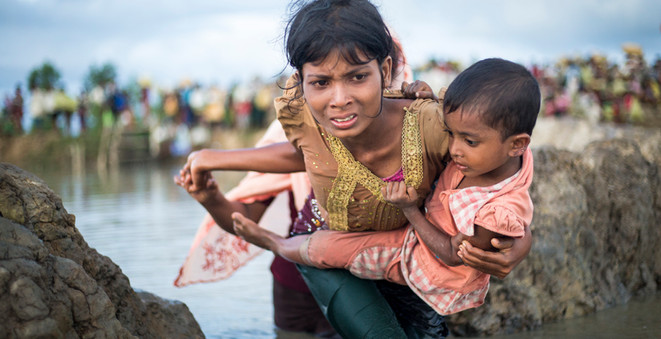 A Rohingya child clings tightly to her mother as they cross the border from Myanmar into Bangladesh, near the village of Anjuman Para in Palong Khali.  To reach Bangladesh, the Rohinyga walked for days, many carrying children. They waded through marshland before swimming across the Naf river that divides the two countries.   © UNHCR/Roger Arnold