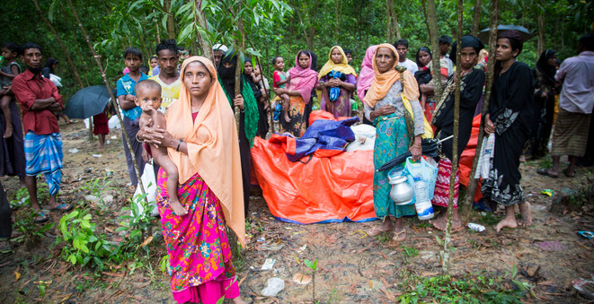 After walking for days through the forest to escape violence in Myanmar, a group of newly arrived Rohingya refugees wait for help at the side of the road outside Kutupalong refugee settlement in Cox's Bazar, Bangladesh.  © UNHCR/Roger Arnold
