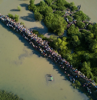 An aerial shot shows thousands of new Rohingya refugee arrivals crossing the border near Anjuman Para village, Palong Khali, Bangladesh.  © UNHCR/Roger Arnold