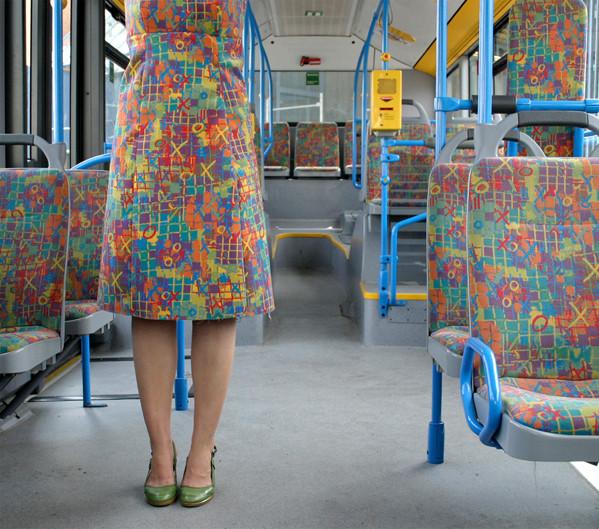 Elle s'habille et se camoufle avec les tissus de bus.