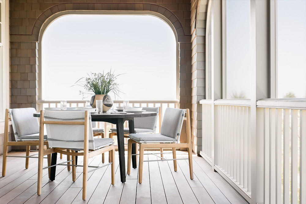 Charming bright and airy Modern Farmhouse Deck. View of the Atlantic Ocean. Light Timber Chairs. Dark Timber Round Table.