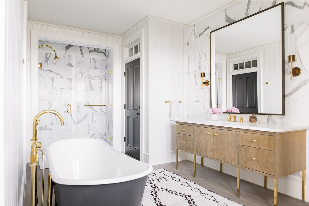 Charming bright and airy Modern Farmhouse Bathroom. Black and White Clawfoot Bathtub. Marble Shower. Brass Hardware. Timber and Marble Vanity. Brass Wall Sconces. Timber Floors. Beni Ourain Rug.