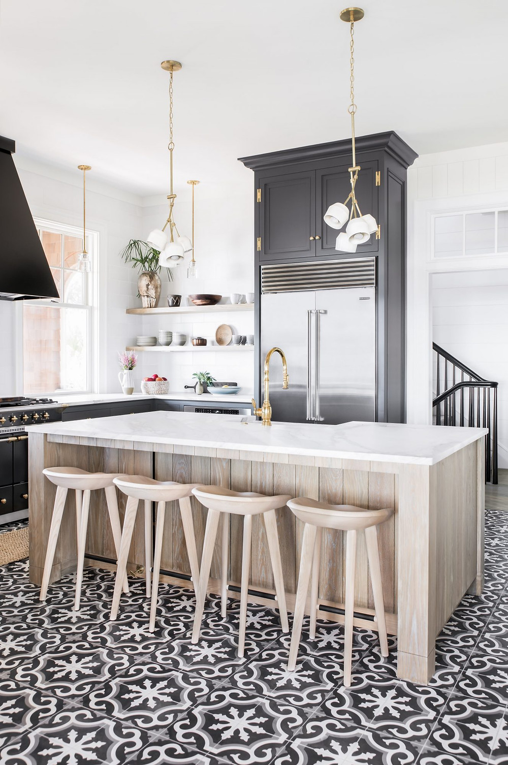 Charming bright and airy Modern Farmhouse Kitchen. Brass Hardware. Timber and Marble Kitchen Island. Black Cupboards. Spanish Tile Floors. Open Shelving.