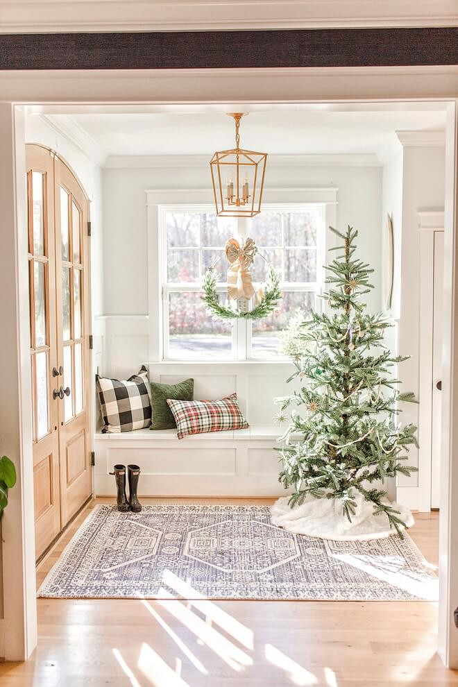 Christmas in July. Modern country home with built in window seating and shaker cabinetry complete with plaid cushions. A lightly flocked undecorated rustic christmas tree sits in corner with white Christmas skirt and vintage rug beneath.