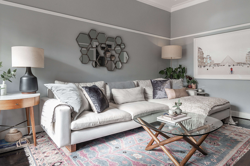 Light grey painted walls, large photo artwork of the Louvre in Paris, pale blue and dusty pink rug, midcentury coffee table, decorative mirror.