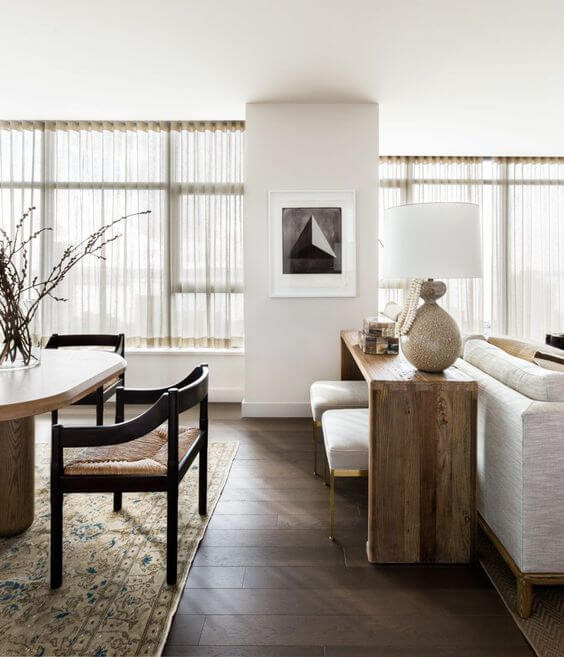 A view of the space that holds an open dining room and a lounge room. Sheer curtains cover a wall of windows. Dark walnut floors have a vintage rug sit atop. The dining room table is a light timber and oval shaped surrounded by dark timber arm dining chairs. A lighter mango wood console sits behind a white fabric sofa and a table lamp sits on top with fabric stools sat beneath.