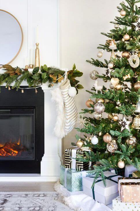 A christmas tree sits in the corner next to a tastefully decorated mantle adorned with pine garland, twinkle lights and brass candle holders of various size and shape with pillar candles, complete with a moder round brass mirror in the centre. The Christmas tree has many presents surrounding. Christmas in July.