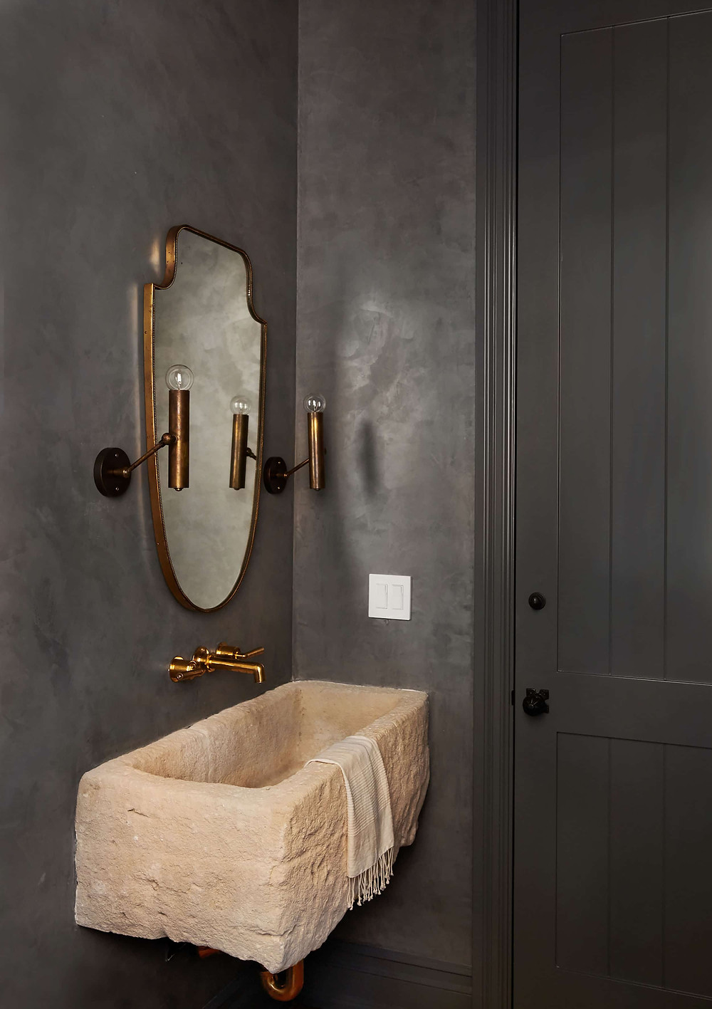 A fresh bathroom in a deep grey for the walls, trim and door. A rough cut stone sink hangs on the wall with exposed brass pipes and wall mounted brass taps. A traditional brass mirror hangs on the wall flanked by brass sconces. The effect is English Countryside with a modern twist.