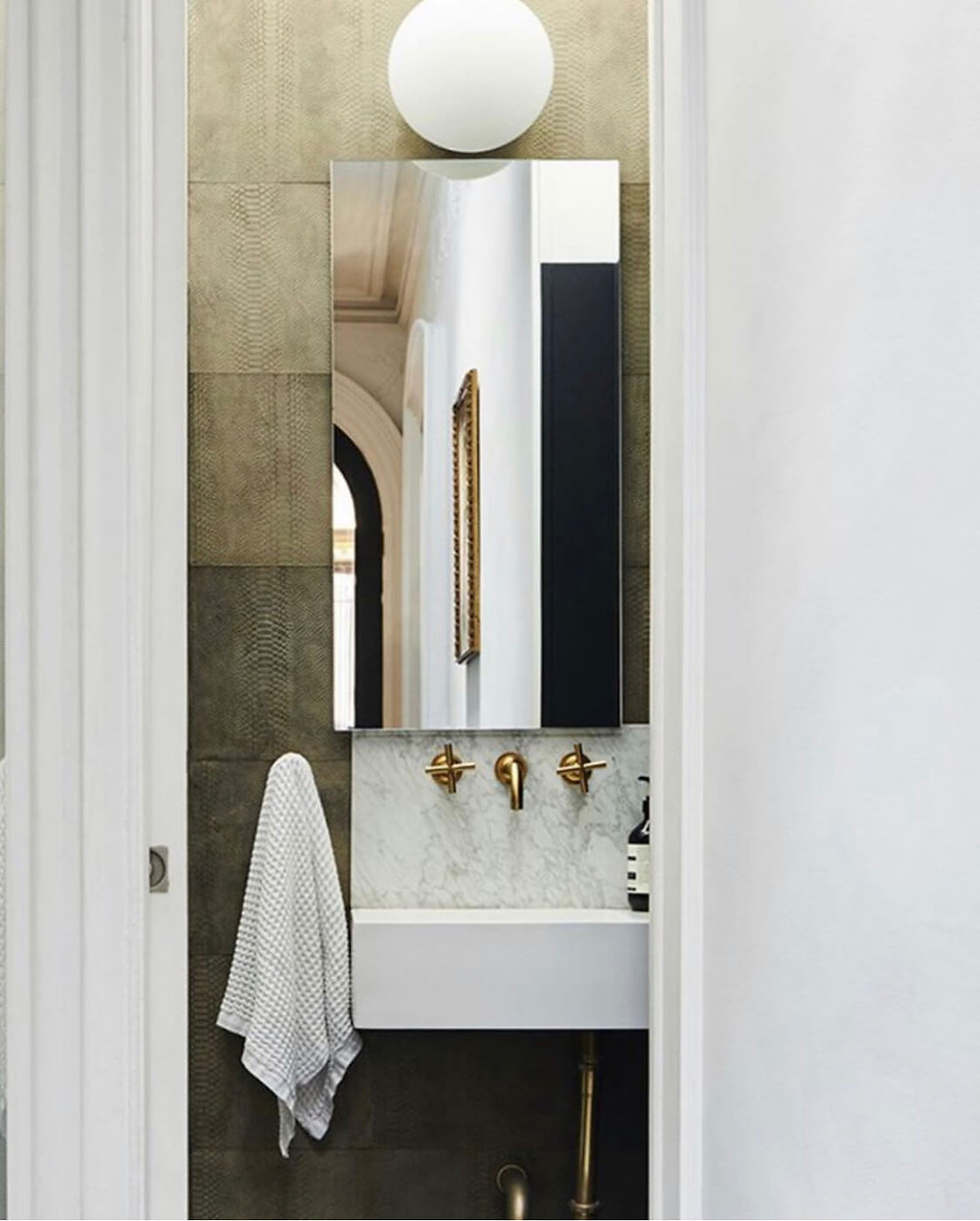 A powder room with walls adorned with textural taupe leather tiles. A round wall mounted globe sconce sits above an off centred rectangle frameless mirror. Below is a small marble backsplash with wall mounted brass tapware and a small white wall mounted ceramic sink with exposed brass pipe work. A white hand towel hangs directly left. In the mirror, reflects a hallway with a brass frame and black arched door with opulent crown mouldings.