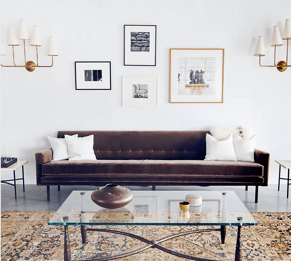 Vintage rug with glass coffee table. Minimalist gallery wall with wall sconces. Velvet mid-century sofa.