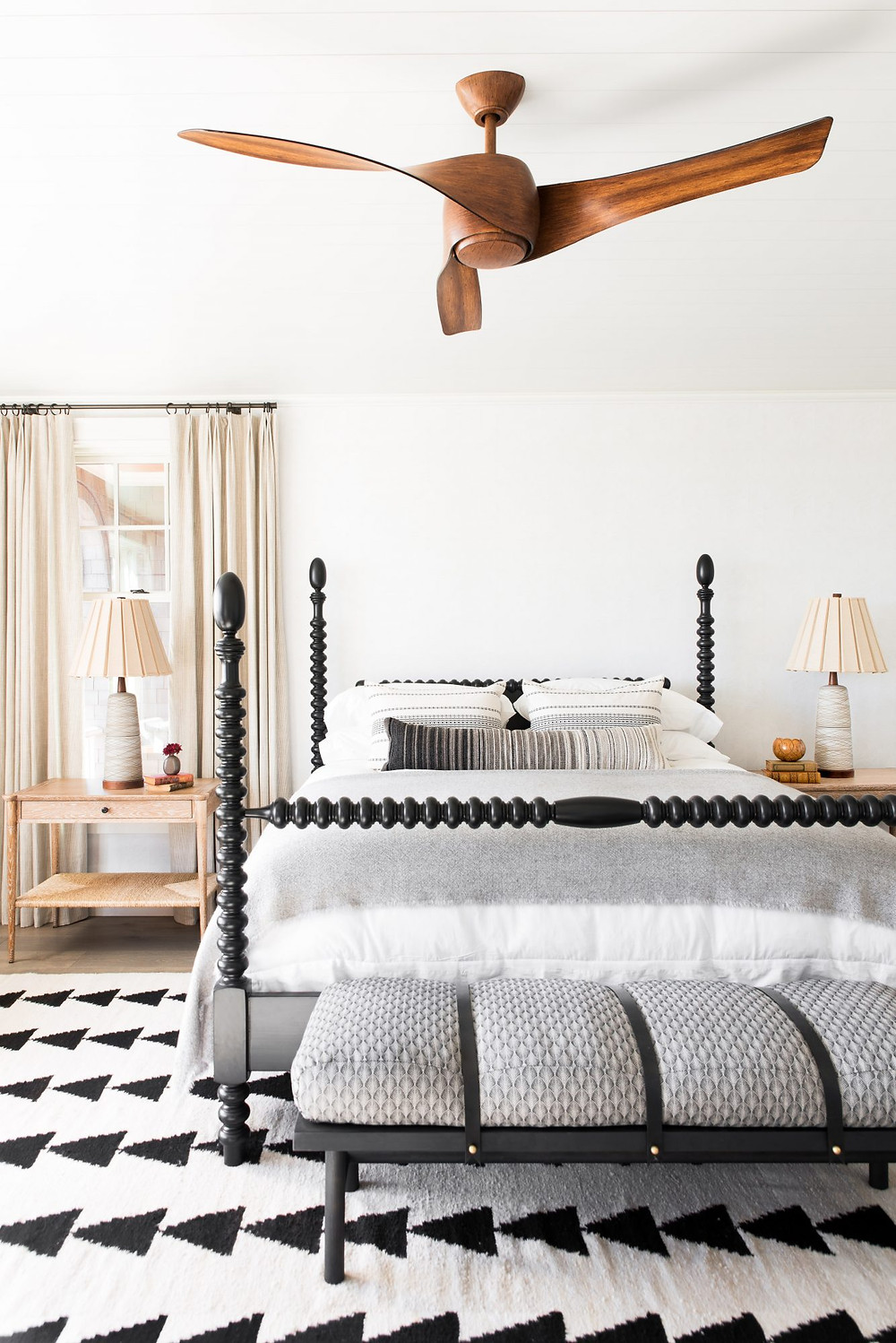 Spacious bright and airy Modern Farmhouse Bedroom. Timber Floors. Modern Timber Ceiling Fan. View of Atlantic Ocean.Beige Drapes. Black and White natural Rug. Black Spindle Bed with Bench.